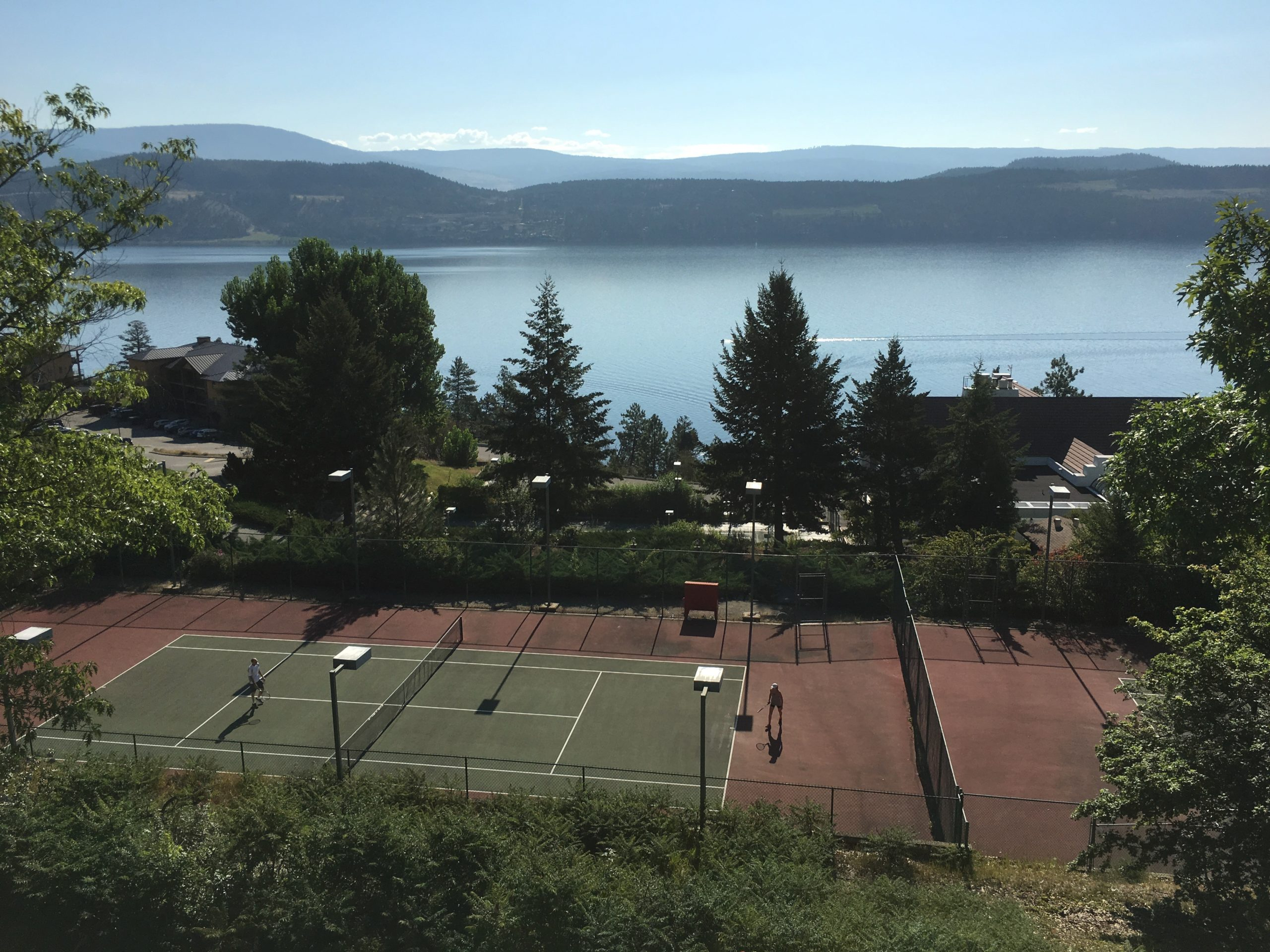 Playing Tennis On The Tennis Court Located At Okanagan Beach Club