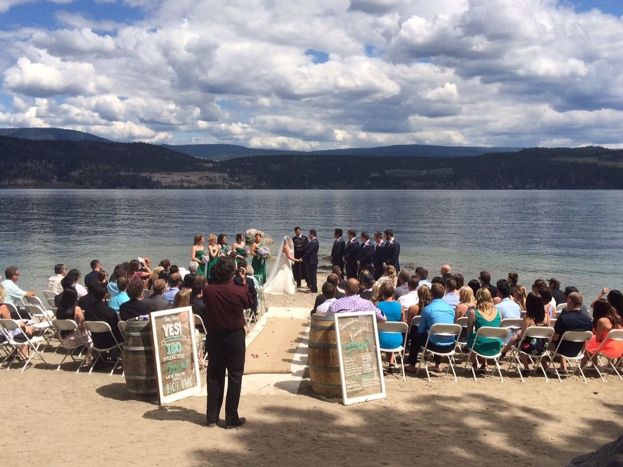 People Gathered For Wedding Ceremony On The Beach Next To Okanagan Lake